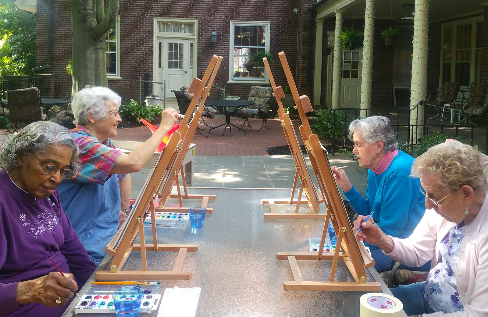 Residents enjoy painting on the patio.