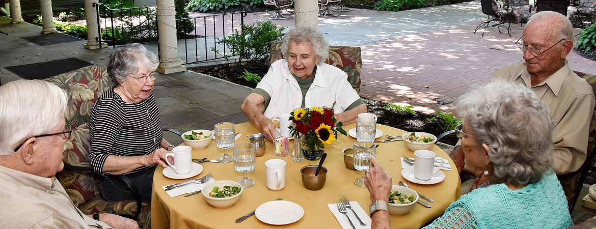 Image of a group of seniors enjoying the lifestyle and a meal together at The Hickman