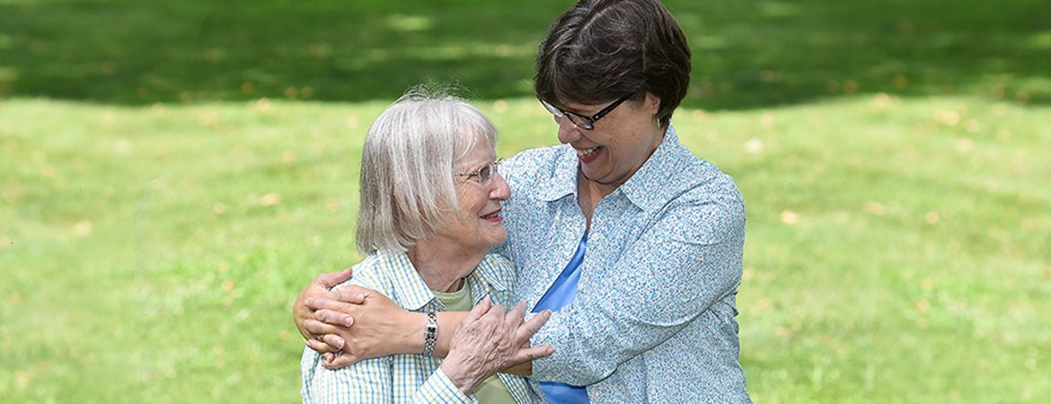 Image of a woman hugging a senior who is part of the short-term respite care offered at The Hickman