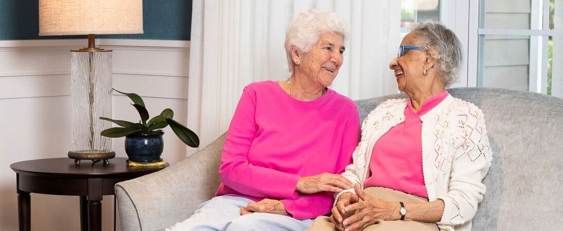 Image of two senior women sitting on a sofa, happy about the personal care at The Hickman