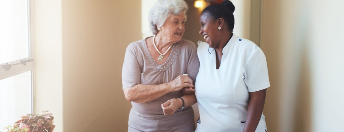 A senior and a personal care worker smiling and talking to each other.