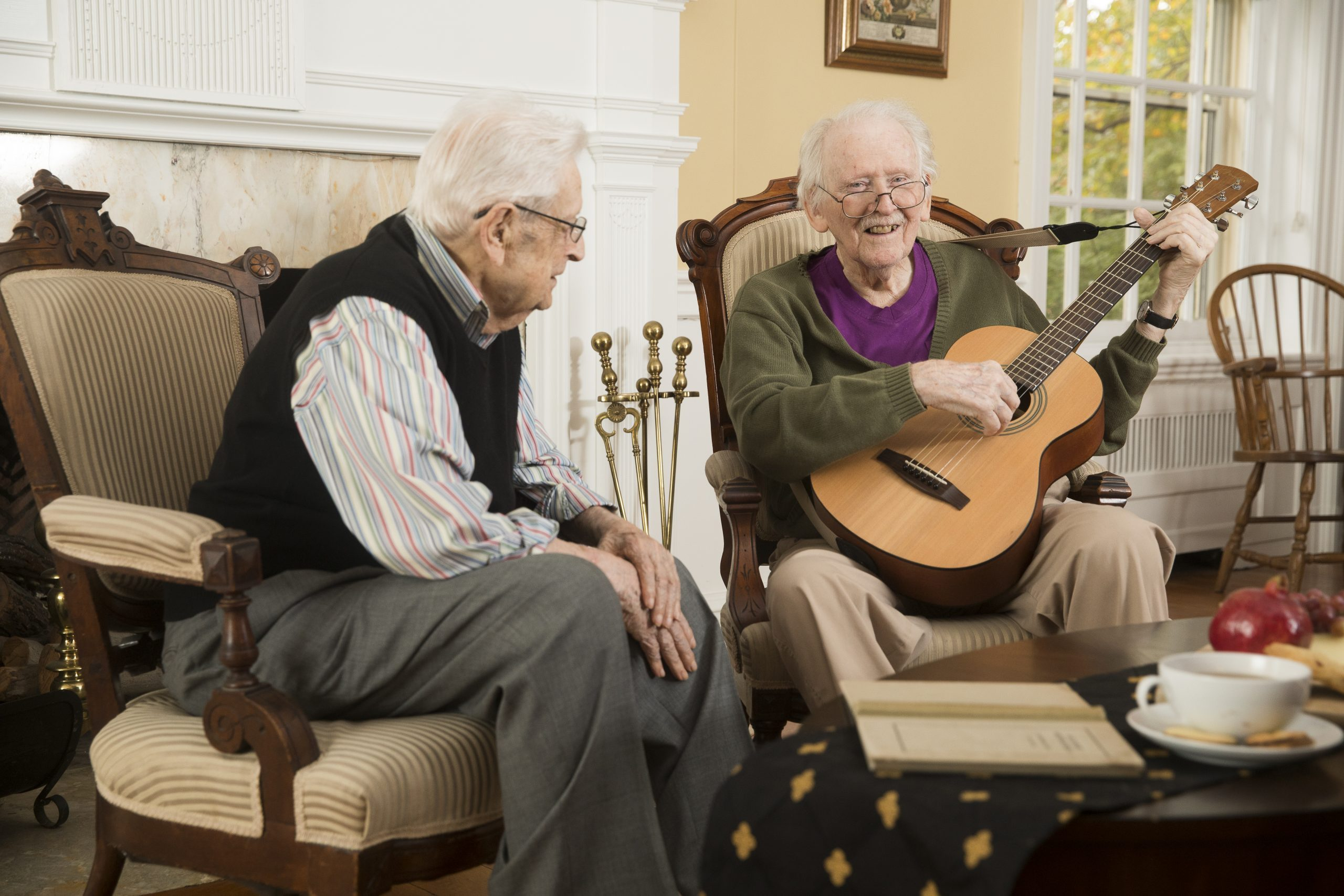 Male resident of The Hickman playing the guitar for another resident.